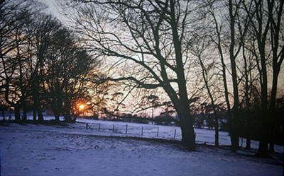 A view taken in the 1960s of snow covered   countryside near Henley   with the sun rising/setting (?) in the distance.    Photo kindly provided by Roy Sadler.